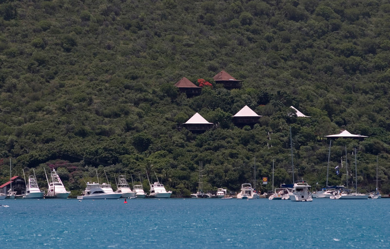 The distinctive bungalo rooftops of the Bitter End Yacht Club and Resort nestled into a lush green hillside on John O'Point, Virgin Gorda, British Virgin Islands (BVI), West Indies, Caribbean.