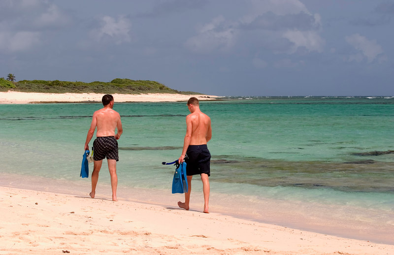 Snorkelers walk the beach at Loblolly bay, North Shore, Anegada, British Virgin Islands (BVI), West Indies, Caribbean