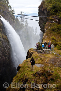 Hikers photograph at a scenic overlook, waterfall and fishery pipes (part of NSRAA Deer Lake Station project) in Mist Cove, Chatham Strait, Inside Passage, southeast Alaska, USA.