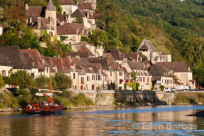 Sightseeing river boat and the cliffside village of la Roque Gageac, Dordogne River, France.