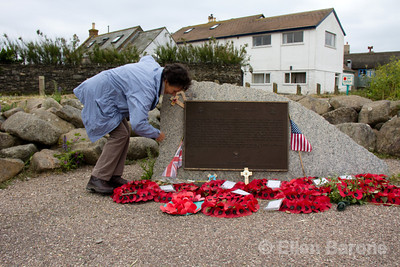 Wayfarers guide, Muff Dudgeon, places flowers on the at the Torcross memorial, Slapton Sands beach, Devon, England, U.K..