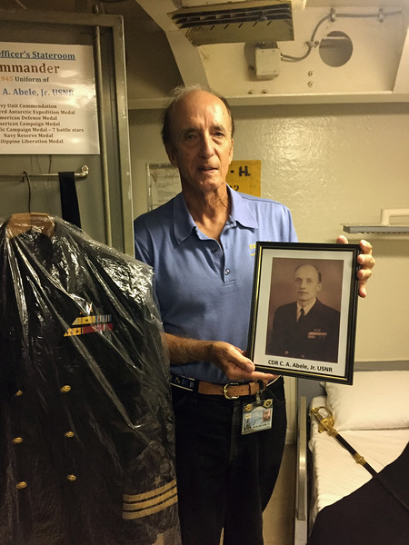 """Captain Rich Abele,  4th generation naval officer, shows displays his fathers picture.  The Commander's Cabin is a memorial to Rich's father, who was a Navy Captain, having served in Guadalcanal and  Philippines campaigns. The brass plaque outside the cabin is affixed to the bulkhead in perpetuity.  This stateroom will be """"The Abele Stateroom"""" as long as the IOWA remains afloat as a museum ship.  All the uniforms and other memorabilia in the stateroom are from 1945."""
