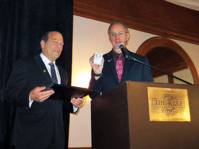 """Steve Elkins accepting a plaque of appreciation and a medallion, purported to be a """"chick magnet"""", from Larry Schutte."""