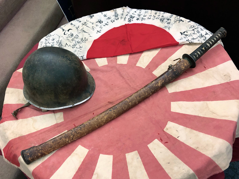 Roy Roush, WWII veteran, shares war relics; his combat helmet, Japanese regimental flag, personal Japanese officer's flag, a 15th century sword taken from a Japanese officer.<br /> ACLA 75th D-Day anniversary commemoration<br /> June 6, 2019