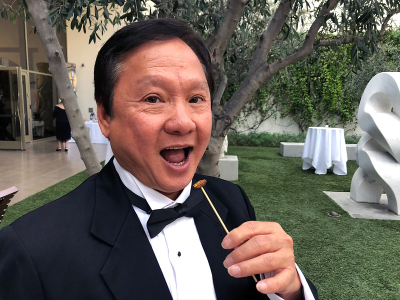 Paul Wong trying out a bug appetizer<br /> Night of High Adventure<br /> Bowers Museum, November 2, 2019