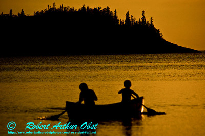 Orange after-glow of sunset over youth canoeists silhouetted on Lake Superior's Gargantua Bay within Lake Superior Provencial Park (Canada ON Wawa)