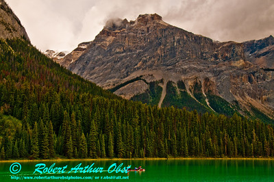 Canoe on Emerald Lake guarded by the President Mountain Range and Top Hat Peak near Field within Yoho National Park (CAN BC Field)