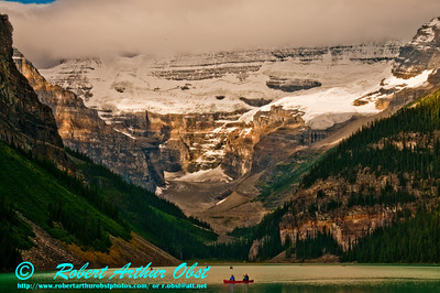 Glaciated mountains and hiking trails to the sky surround canoeists on the emerald and serene Lake Louise (Canada Alberta Lake Louise)