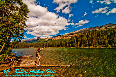 View from canoe of a youth balancing act on crystalline emerald Honeymoon Lake near the Icefields Parkway within Jasper National Park (Canada Alberta Jasper)