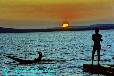 Sunset silhouetting a pirouetting lake canoeist near the Matawaska River (Canada, Ontario)