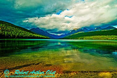 Canoeist's view of glaciated peaks encircling crystalline serene colorful Bowman Lake within Glacier National Park (USA MT Polebridge)