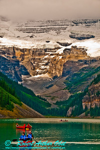 Glaciated mountains and a network of hiking trails encircle canoeists on emerald Lake Louise (Canada Alberta Lake Louise)