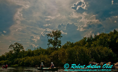 Boiling blue clouds over sun rippled riffles and canoeists on the Wild Scenic Wolf River (USA WI White Lake)