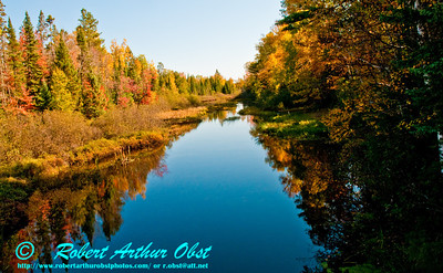 View from a canoe of autumn reflections under blue skies over the Wisconsin River Headwaters Near Lake Lac Vieux Desert (USA WI Land O'Lakes)