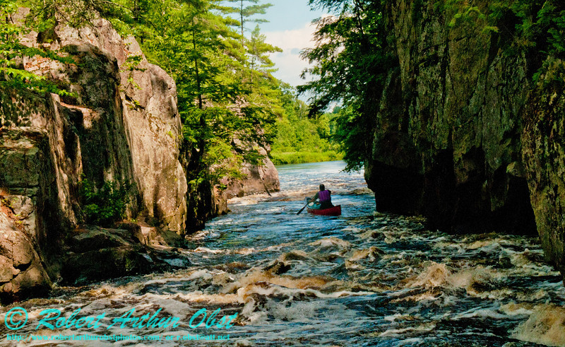 Mossy granite cliffs frame Charles Frisk and his open canoe within the beautiful Dalles of the Wolf at a river flow of 744 CFS on the wild Wolf River Section 4 within Menominee Indian Nation or Menominee County  (USA WI Keshena)