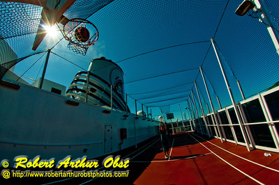 Under incredible cerulean blue skies and dazzling light, a talented youth swooshes a basketball with sun stars on Sports Deck Nine of the Holland America Zaandam cruise ship (USA Alaska Inside Passage near Ketchikan)