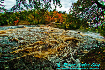 A rain swollen Presque Isle River roars over Manido Falls north of South Boundary Road during autumn (USA MI Ontonagon)