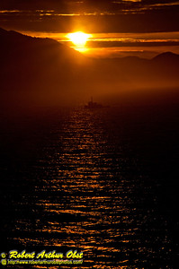 Holland America Zaandam ship cruises through dark waters through mist past a lonely fishing boat and a spectacular orange sunset over mountains within the Inside Passage of the Pacific Ocean between Ketchikan and Juneau Alaska (USA Alaska Ketchikan)