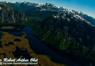 Rugged snow covered mountains and deep blue lakes and green marshlands within Misty Fiords National Monument (USA Alaska Ketchikan)