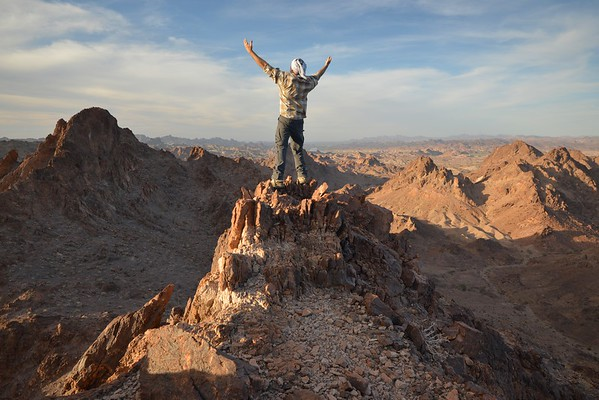 Climber With Outstretched Arms on the Summit