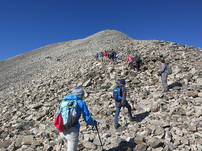 Climbers are in the foreground, middle distance, and far distance.