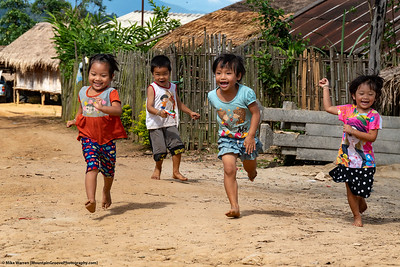 #11.  Backstory:   A little boy teases 3 little girls, who take off running, in this October image taking on a visit to a Lahu hill tribe village and school in Northern Thailand.