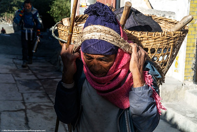 #25.  Backstory:  Life is hard in areas of Nepal, as seen on the face of a Nepalese man carrying his tools in a neck basket.