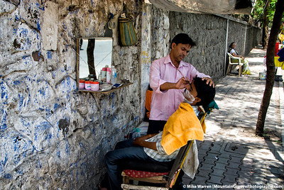 #15 - In India, a land of contradiction, a sidewalk barber shaves a customer.  With a potable chair and mirror, the barber could follow his business.  I found India to be incredibly chaotic, awesome in some ways and very difficult to experience in other ways.   This image was taken in Pune, a city of 5M people, during our quick May visit to India.