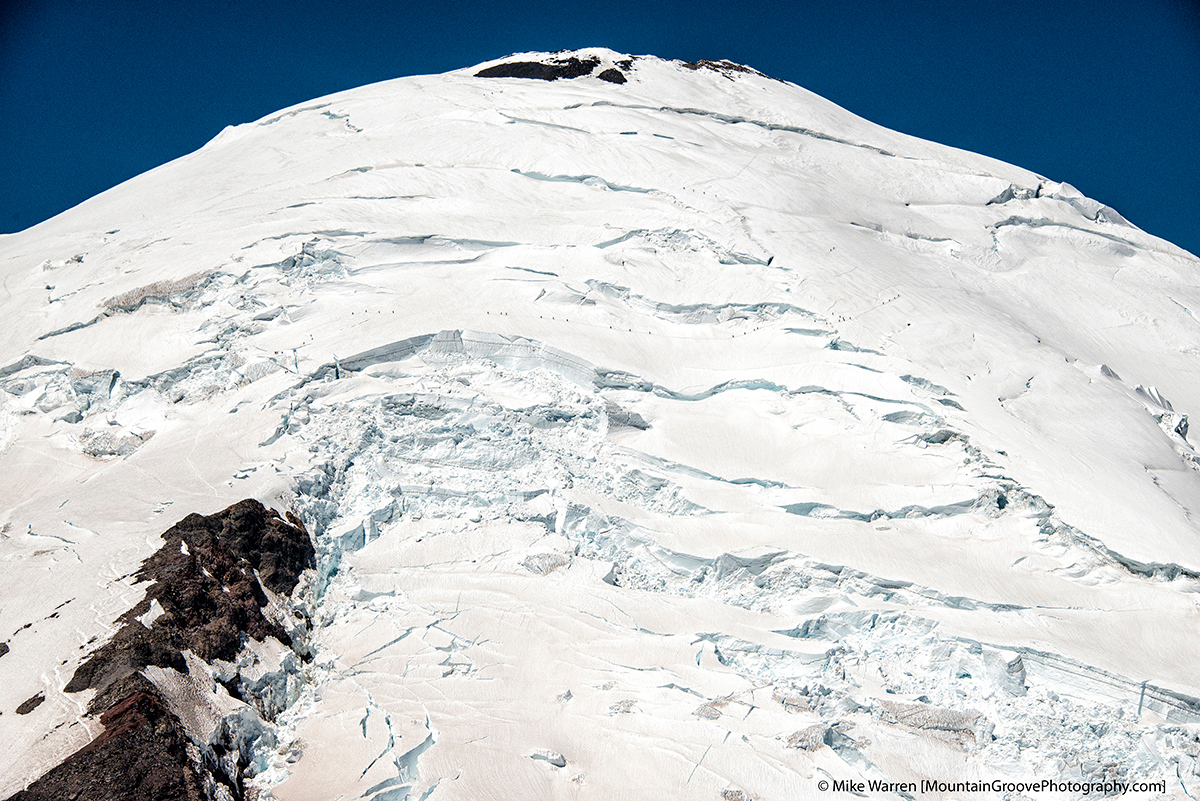 A close look reveals a long line of climbers on the DC route of Rainier