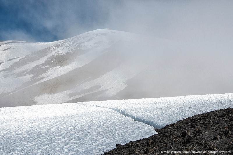 """The summit clears briefly. This is not a crevasse, but the """"path"""" worn by 100s of climbers"""