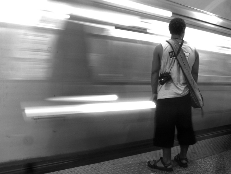 """<h3>8. Riding the El Train</h3> <br> I stand,<br> And all around they move;<br> Processions of society in bustling horde surrounding me.<br> A booming cacophony shaking the ground of voices and cell phones and walking around,<br> <br> Now add a breeze and headlight from the emptiness at left,<br> And the horde around me pushes to the limits of their shelf,<br> And the moment doors are open it's an unrepentant motion<br> Pushing on relentless forward with priority to self!<br> Then a last and final warning """"doors are closing, thanks for boarding""""<br> And a quick acceleration leads away the mass of man, and -<br> I stand.<br>"""
