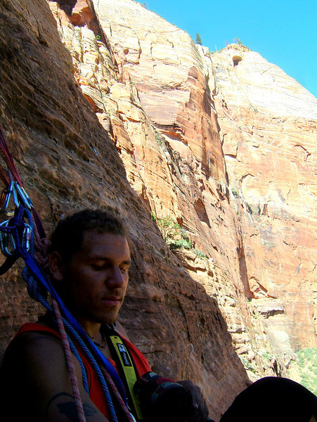 A shaded belay ledge offers Kelsey a brief respite from the heat and work.