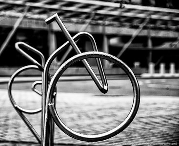 Abstract bike racks in a row, when viewed from the side make up a bicycle!
