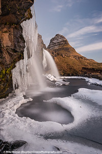 Kirkjufell Mountain, partially frozen waterfall in the foreground.