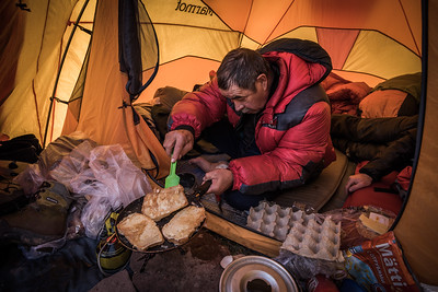 Vladimir cooking at Advanced Base Camp, Zaalay range, Pamir, Kyrgyzstan