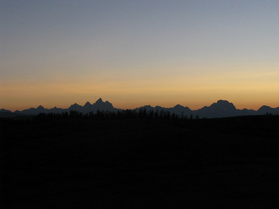 First view of the Tetons, entering at dusk from the east over Togwotee Pass. The Grand Teton is high point left of center; Mt Moran much farther to right.