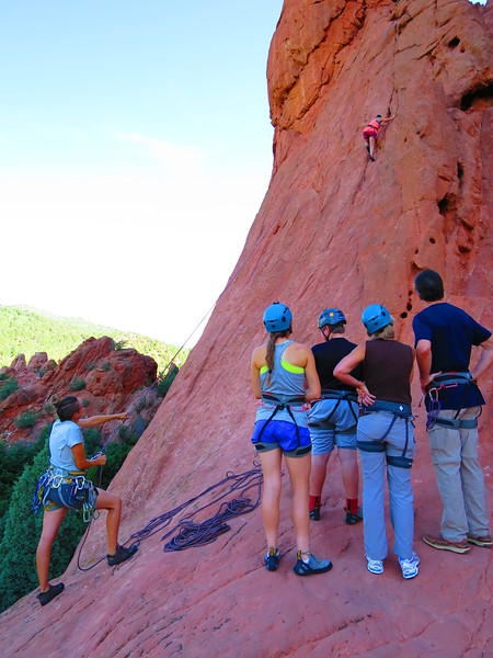 A family outing with a rock climbing guide handling the belay.