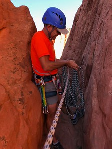 Off rappel and now coiling our 200-ft rope; the five quick-draws clipped in his harness.
