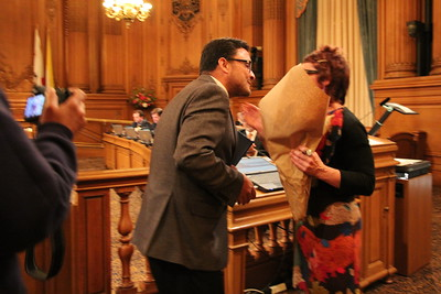 Supervisor David Campos gives Laura a bouquet of flowers and her award certificate.