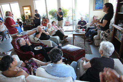 Back room, Left to right: Bruce Bonacker (white shirt), Paul Wermer (blue shirt), Michael Hamman (red shirt, blue apron).  Seated in front on the red leather recliner - Gerry Crowley.  Also seated, right to left are Marlayne Morgan (clapping), Kris Schaeffer (looking down).  Against the back wall are Jamie Whitaker (blue shirt, standing), Ed Uyeshima (orange shirt, sitting).  Seated closest to the camera are Leah Taylor Pimentel, Aaron Peskin and Judith.