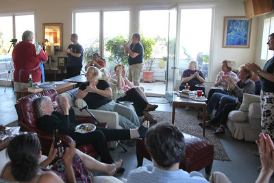 Back room, Left to right: Michael Hamman (red shirt, blue apron), Jamie Whitaker (blue shirt, standing), Ed Uyeshima (orange shirt, sitting).  Seated in front on the red leather recliner - Gerry Crowley.  Also seated, right to left are Marlayne Morgan (clapping), Kris Schaeffer (looking down).  On coach, closet to camera, left to right: Leah Taylor Pimentel, Aaron Peskin.