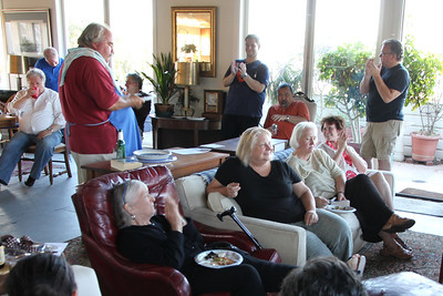 Back room, Left to right: Bruce Bonacker (white shirt), Paul Wermer (blue shirt), Michael Hamman (red shirt, blue apron).  Seated in front on the red leather recliner - Gerry Crowley.  Also seated, right to left are Marlayne Morgan (clapping), Kris Schaeffer (looking down).  Against the back wall are Jamie Whitaker (blue shirt, standing), Ed Uyeshima (orange shirt, sitting).