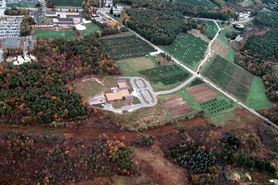 The Mack's farm stand can be seen in the upper right hand corner of the image.  Mack's U-Pick one is about halfway on the dirt road between the entrance to Moose Hill School and  the farm.  You can see the cars parked there.  Matthew Thornton is in the upper left corner, the Town Common has the dark trees on it near the center top of the image.
