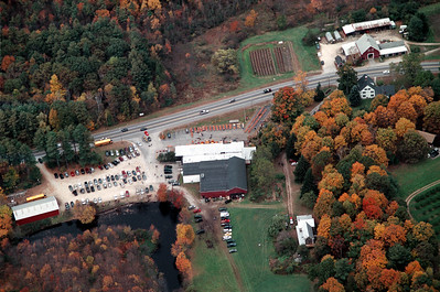 The majestic white farmhouse on the right is the homestead now home to Carol and Andy Mack.  Carol is the Principal of Matthew Thornton, Andy is a on air personality.  Across the street in what looks like a happy wide open face is a classic New England Barn.  The shed behind contains is used to shelter sprayers and tractors when not in use.