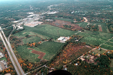"Still not showing the entire farm this view provides a glimpse from what is hidden from cars as they travel up route 93 from Boston just 43 miles away.  The terraced looking orchard on the right hand side towards the center is Mack's U-Pick 4.  The orchard has been grown on the side of the slope.  On clear days you can see Boston from the high points of Woodmont Orchard.  The line in the center near the top is 102 leading to crossroads mall at the end.  South school can be seen to the left of that directly above the Market Basket plaza in the distance.  To the far right the dome shaped image surrounded by smaller domes, is the VOR called ""MHT"" used for aircraft navigation."