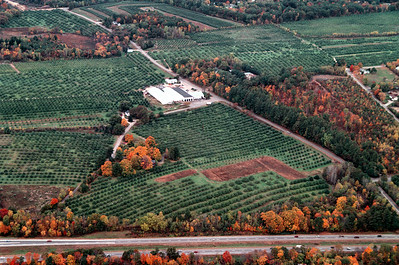 Woodmont Orchards viewing the farm to the west just above the Route 93 exit 4 off ramp.  The red car is about to exit onto Route 102 in this photo.  The Woodmont homestead is completely covered with the fall foliage in this view, but the climate controlled storage house can be seen clearly in the center.  The loading dock doors show as teeth under the black roof.  The farm continues off to the right along Hovey Road up to Spring Road not seen in this image.