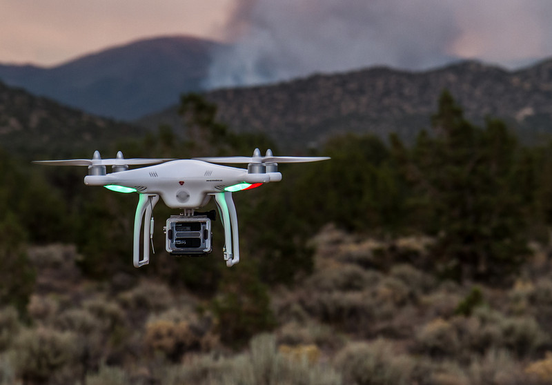 """Bison Fire Thursday July 4, 2013 (IMG4499)  Landing the DJI Phantom multirotor aerial platform after taking aerial photographs and video of the fire area. The Bison fire is seen burning in the background.  <a href=""""http://youtu.be/ZpKvEmmGjLQ///"""" target=""""_blank"""">Video clip from the DJI Phantom of the fire area</a>"""