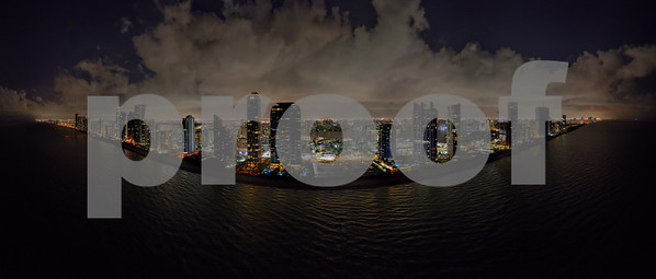 Aerial night drone panoramac photo coastal city highrise tower illuminated