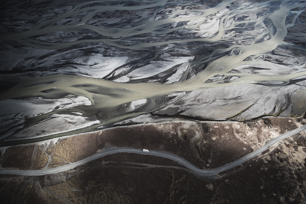 A car drives next to a braided river in Thorsmork, Iceland