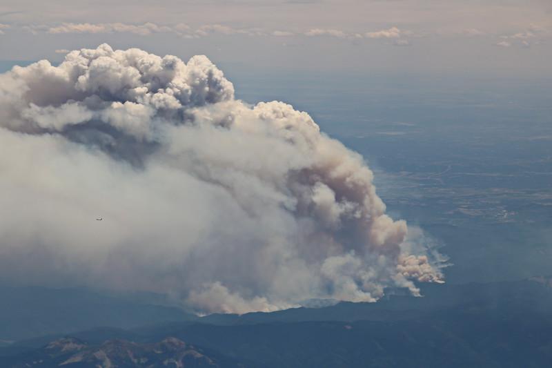 A Plane Flies Close to the Smoke Plume
